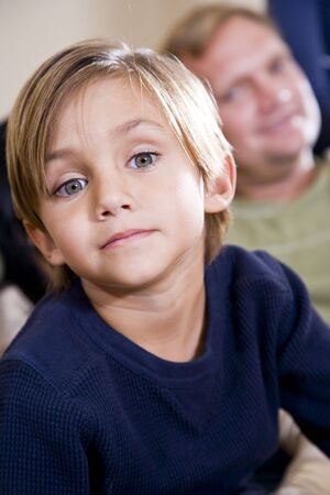 Face of cute 5 year old little boy with father watching in background