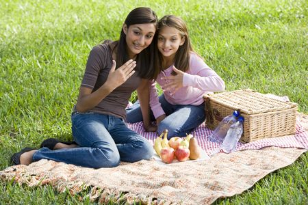 younger: Teenage girl and younger sister enjoying  picnic in the park Stock Photo