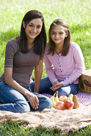 Teenage girl and younger sister enjoying picnic in the park photo