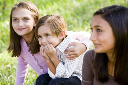 Cute 5 year old little boy with affectionate older sisters together on grass outdoors photo