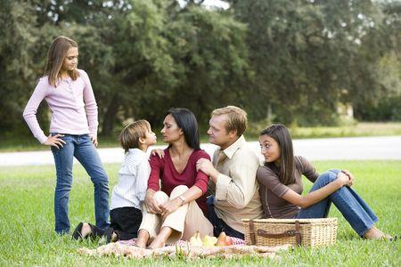 Interracial family enjoying a picnic in the park photo