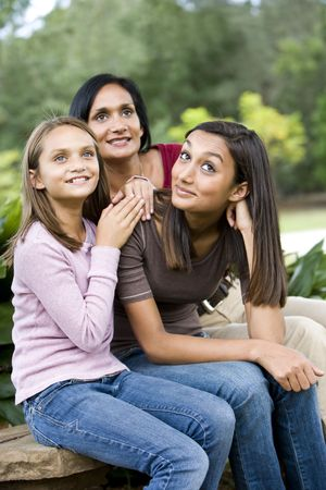 Affectionate Indian mother and two beautiful mixed-race daughters sitting together photo