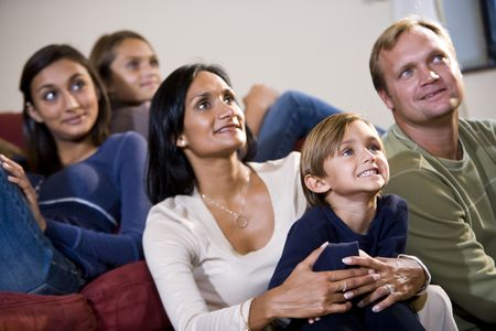 Interracial family of five sitting together on sofa looking up watching TV