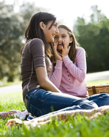 Girls whispering to each other at picnic in park photo