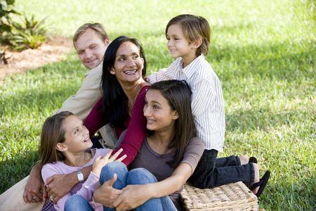공원에서 피크닉을 즐기는 세 자녀와 함께 행복한이 인종 가족
