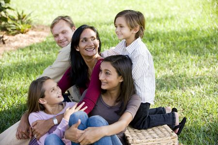 Happy interracial family with three children enjoying a picnic in the park