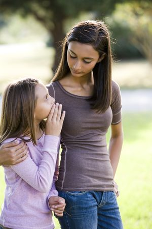Ten year old girl whispering to her older teenage sister while walking outdoors photo
