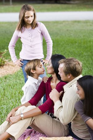 Affectionate interracial family of five enjoying picnic together in park photo