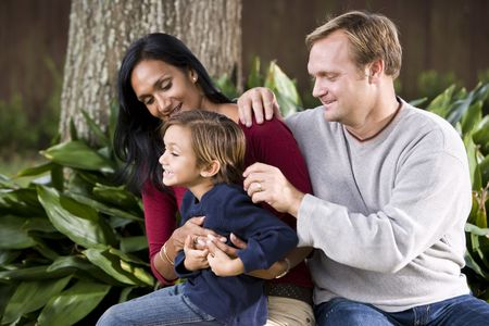 Affectionate Interracial family sitting on bench outdoors with cute five year old boy photo