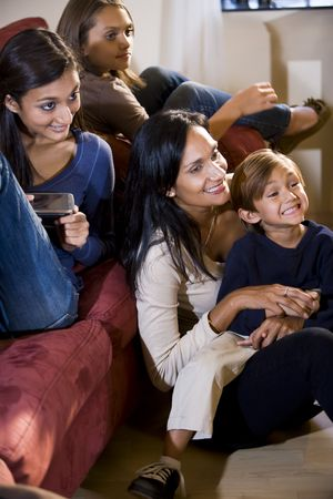 Mother and three children sitting together on living room sofa watching television photo