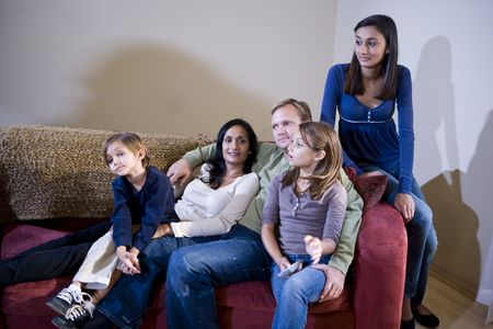 Interracial family of five sitting together at home on living room sofa photo