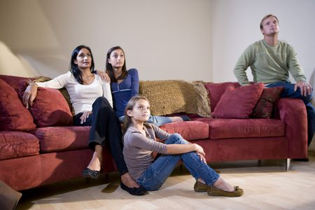 Interracial family of four sitting together on living room sofa watching television