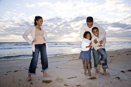 Happy African-American family with two children hugging on beach photo