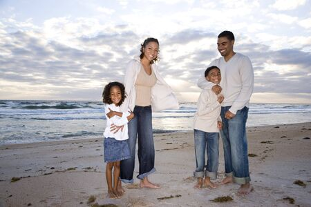 africanamerican: Happy African-American family with two children hugging on beach