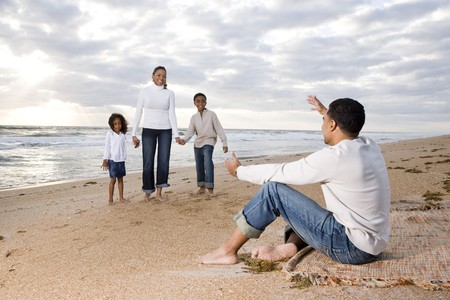Happy African-American family of four on beach, father waiting with open arms photo