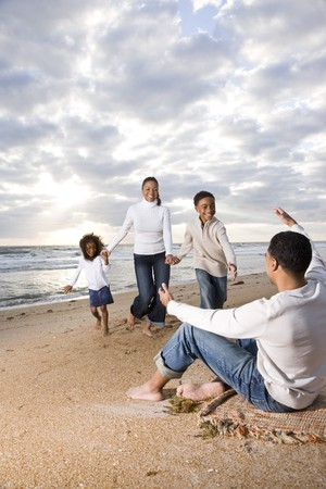 Happy African-American family running to father on beach photo