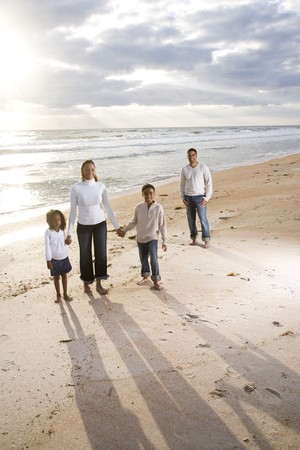 Happy African-American family of four standing on beach with beautiful sunlight photo
