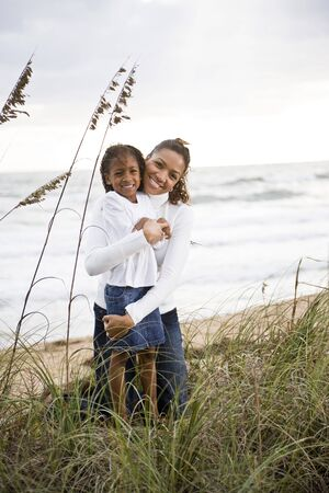 Happy African-American mother hugging six year old daughter at beach photo