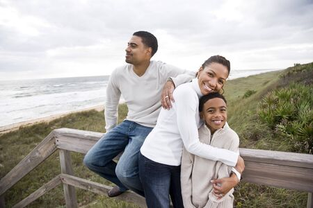 Happy African-American parents with ten year old boy smiling and hugging at beach photo