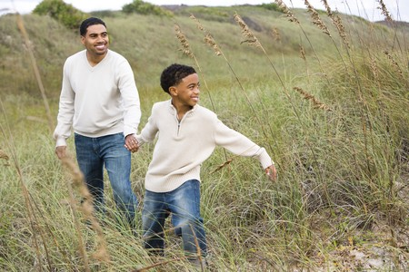 Happy African-American father and son walking together along sand dunes and grass at beach