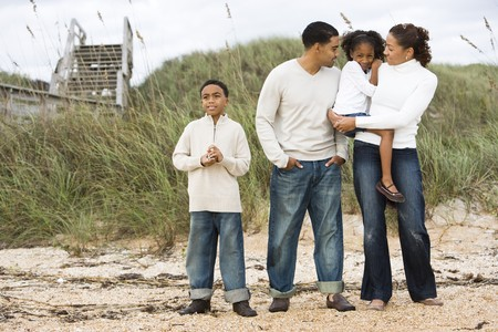 Happy African-American family with two children standing together on beach photo
