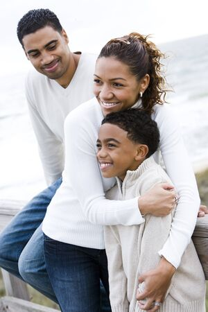 Ten year old African-American boy with parents at beach photo