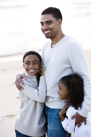 Happy African-American father,  ten year old son and six year old daughter standing on beach Stock Photo - 6926055