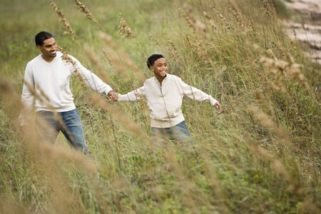 sea oats: African-American father and ten year old boy walking through sea oats grass at beach Stock Photo
