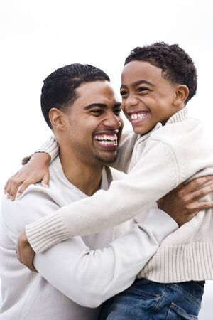 Happy African-American father hugging and laughing with ten year old boy photo