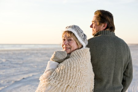 waistup: Cari�osa pareja senior en su�teres juntos en la playa