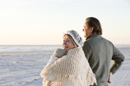 winter woman: Affectionate senior couple in sweaters together on beach