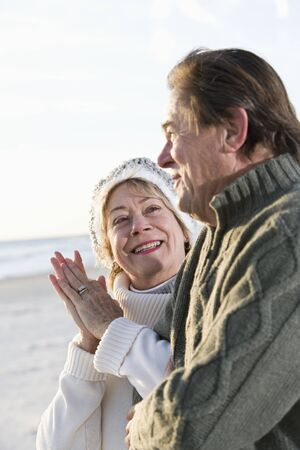 Affectionate senior couple in warm clothing standing together on beach photo