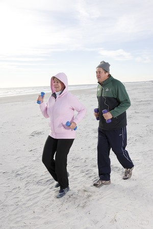 Senior couple exercising, jogging on beach with hand weights photo