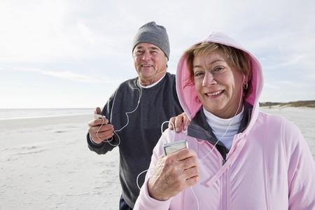 ecoute active: Couple senior, �couter de la musique sur un lecteur MP3 sur la plage  Banque d'images