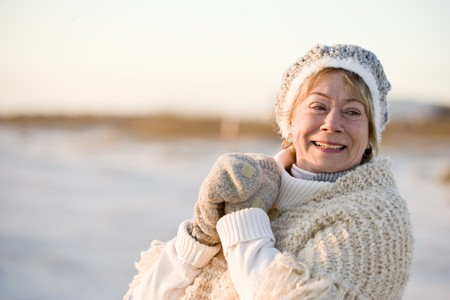 smiing: Portrait of senior woman wearing warm winter hat, sweater and gloves Stock Photo