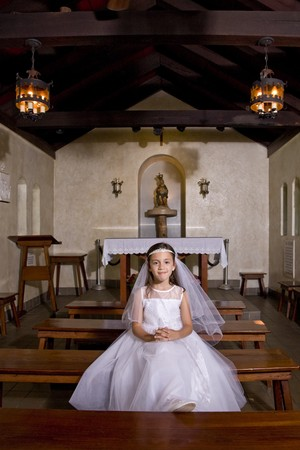 Portrait of young girl in church wearing first communion dress photo