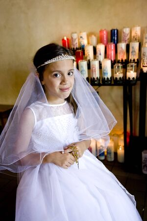 religious clothing: Portrait of young girl in church wearing first communion dress holding rosary beads