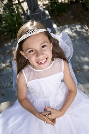 Young girl outdoors wearing first communion dress holding rosary beads