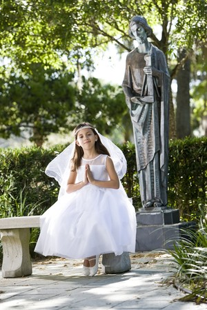 Beautiful child wearing formal white dress on park bench photo