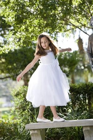 Beautiful child wearing formal white dress playing on park bench Reklamní fotografie