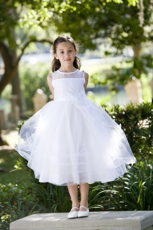 formal clothing: Beautiful child wearing formal white dress standing on park bench Stock Photo