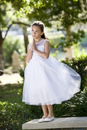 Beautiful child wearing formal white dress posing on park bench photo