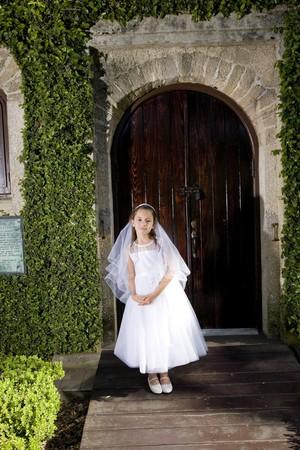 Beautiful child wearing white dress standing outside chapel door photo