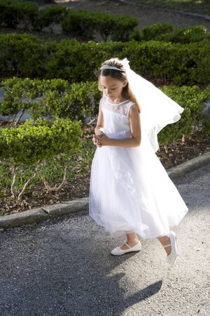 Beautiful 8 year old girl in white dress standing in sunlight holding rosary 免版税图像