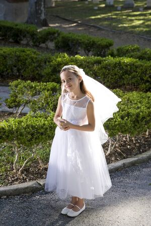 Beautiful 8 year old girl in white dress standing in sunlight holding rosary photo