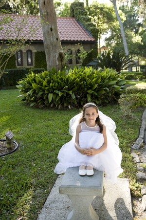 Beautiful 8 year old girl in white dress sitting on bench photo