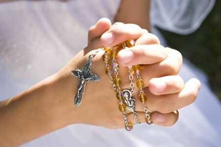 Hands of child holding rosary beads and cross photo