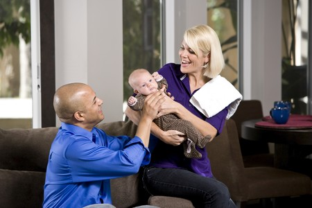 holding close: Dad handing 3 month old baby to mom for feeding Stock Photo