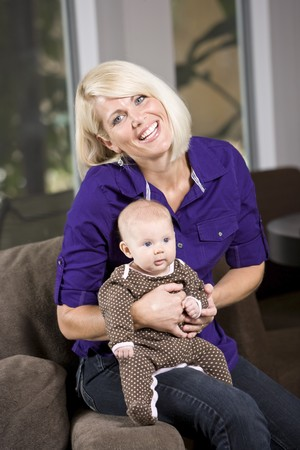 Happy mother holding 3 month old baby on couch at home Stock Photo - 7018809