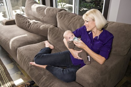 Mother lovingly looking at 3 month old baby drinking bottle on couch at home Stock Photo - 7018861